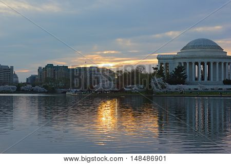 Thomas Jefferson Memorial at sunrise during cherry blossom festival in Washington DC USA. Reflection of the memorial in waters of Tidal Basin.