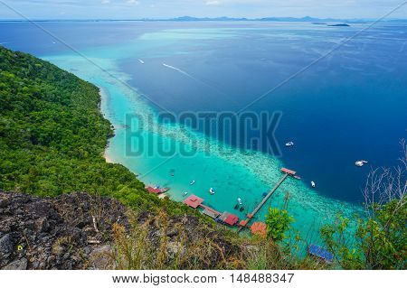 View from the peak of Bohey Dulang Island,Sabah,Borneo.Mirror smooth ocean surrounded by mountains.The bright blue water and rocky shore in the tropical island of Semporna,Sabah,Borneo.