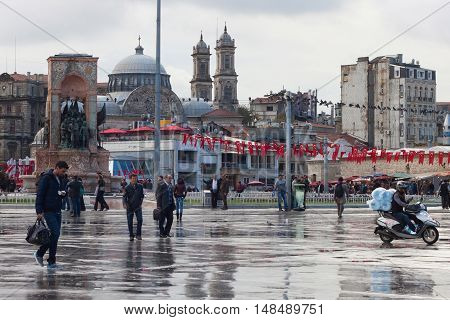 TURKEY ISTANBUL - NOVEMBER 06 2013: Autumn view of famous Taksim square after rain in Istanbul. Taksim is a main transportation hub and a popular destination tourists. Taksim is also a favourite location for public events such as parades or other social g