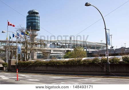 Vancouver, BC - April 20, 2015 - Exiting the Vancouver International Airport on a bight, sunny day with blue skies. Great view of the control tower and the terminal and the Canadian flag and others are blowing in the wind.