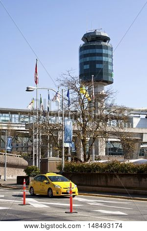 Vancouver, BC - April 20, 2015 - Vertical photo exiting the Vancouver International Airport on a bight, sunny day with blue skies. Great view of the control tower and a yellow taxi . Various flags blowing in the wind.