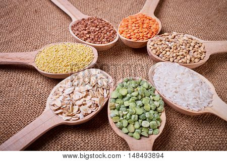 Grains in the spoon, a wooden spoon, a range of cereals, cereals with spoon on cloth, grain yield, organic food, cereal close-up, texture of burlap, kitchen utensils