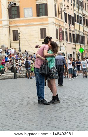 ROME ITALY - JUNE 15 2015: Attractive young couple kissing in Piazza Spagna during their vacation inRome. Italy