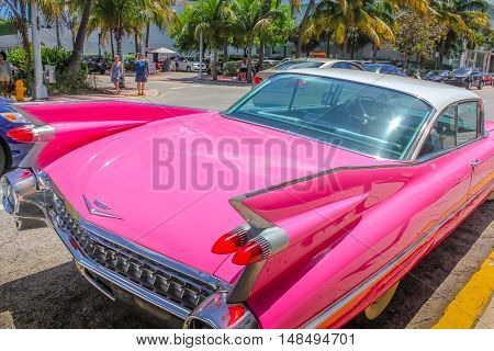 Miami, Florida, United States - April 8, 2012: from behind of the luxurious vintage pink Cadillac Eldorado on a street near Ocean Drive in Miami Beach. Miami Beach is famous for typical classic cars.