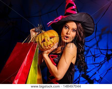 Happy woman holding Halloween shopping bag. Halloween shopping.