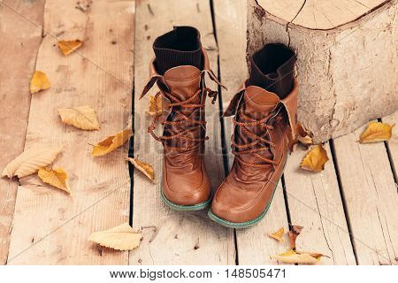Pair of brown boots with socks inside on barn wooden background, autumn seasonal footwear, leather shoes