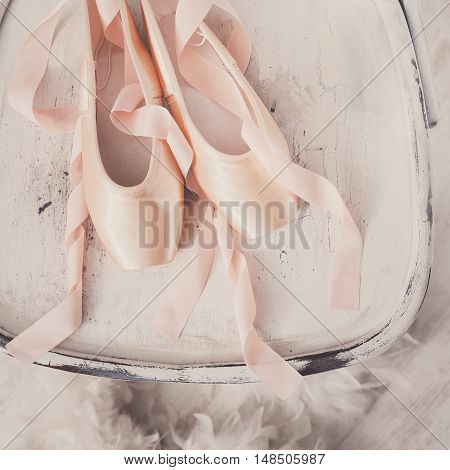 Pastel pink ballet shoes background. New pointe shoes with satin ribbon lay on white rustic shubby chic chair near feather boa, top view from above