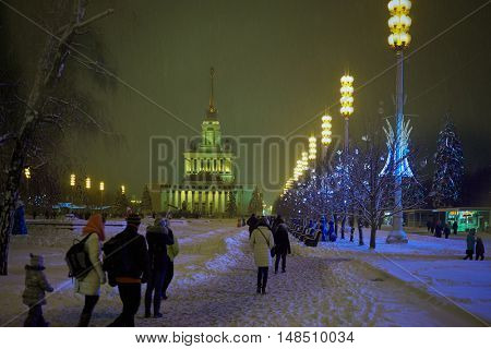 MOSCOW, RUSSIA - JAN 24, 2015: People walk under snowfall in evening at VDNKh. VDNKh is located in Ostankinsky District of Moscow, less than a kilometer from Ostankino Tower.