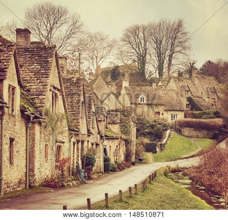 Old street with traditional cottages in Bibury, England, UK. Toned image.