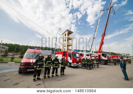 RUSSIA, MOSCOW - MAY 29, 2015: Firemen with fire trucks stand on territory of fire station.