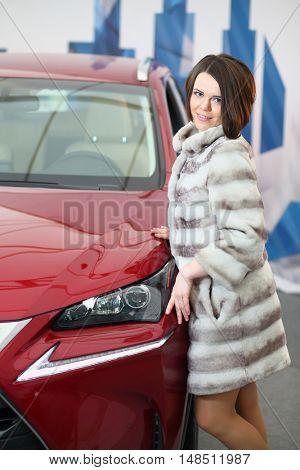 MOSCOW - FEB 14, 2015: Happy beautiful girl (with model release) in a fur standing near the red car in the salon on Russian sixth test drive Lexus Master Class