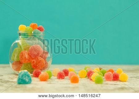 Glass jar full of jelly beans on a wooden table with blue background