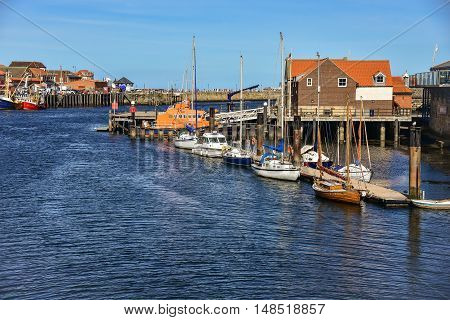 A small yacht and lifeboats at marina in Whitby