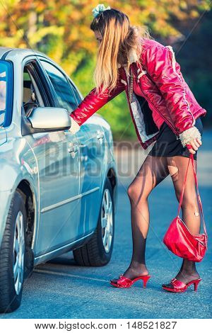 Street prostitute talking to car driver. vertical image, toned image,