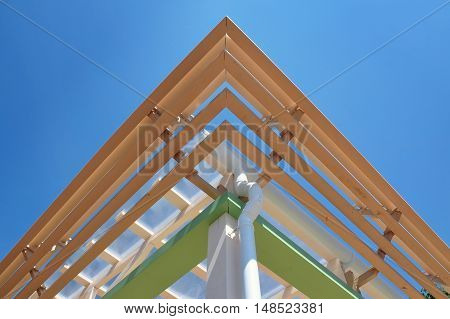 Modern roof construction. Multilevel cornice of the roof of a wooden frame with a drain pipe. Symmetrical view look up.
