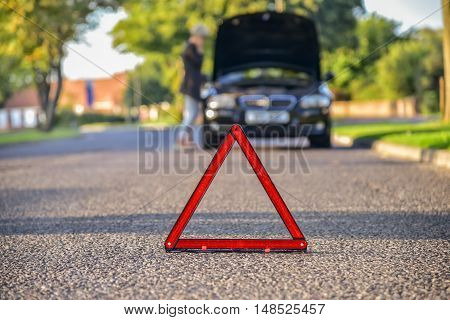 Broken down car with warning triangle waiting for assistance to arrive (shallow depth of field the focus is on the triangle the car is left out of focus).