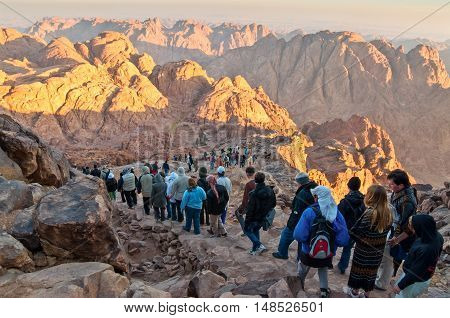 Mount Sinai Egypt - November 25 2010: Pilgrims and tourists on the pathway from the Mount Sinai peak and panorama rocks of Mount Sinai in early morning. According to the Book of Exodus Mount Sinai is the mountain at which the Ten Commandments were given t