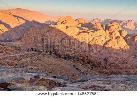 Mount Sinai Egypt - November 25 2010: Pilgrims and tourists on the pathway from the Mount Sinai peak and panorama rocks of Mount Sinai in early morning at November 25 2010. According to the Book of Exodus Mount Sinai is the mountain at which the Ten Comma