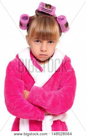 Adorable little girl with in pink bathrobe and hair curlers playing angry wife. Child posing with folded arms, isolated on white background.