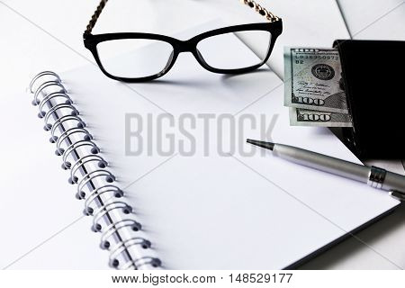 White blank notebook with silver pen and glasses. Some money and wallet are located close to it.