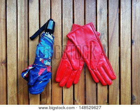 Colored umbrella and red womens leather gloves on wooden boards