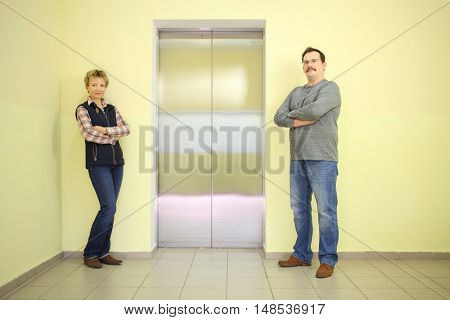 A man with a mustache and a woman standing with hands crossed near the elevator
