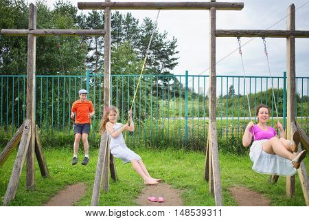 Mother with son and daughter happy swinging on a swing on a wooden playground, focus on boy