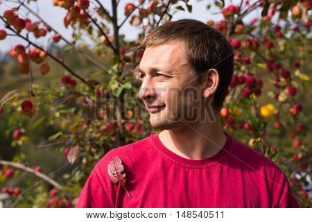 Young man in autumn. Portrait of a young handsome man in a red T-shirt on a sunny day against an apple rennet tree. The sunshine is strong, the shadows are deep.