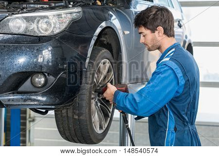 Side view of male mechanic using pneumatic wrench to fix car tire at garage