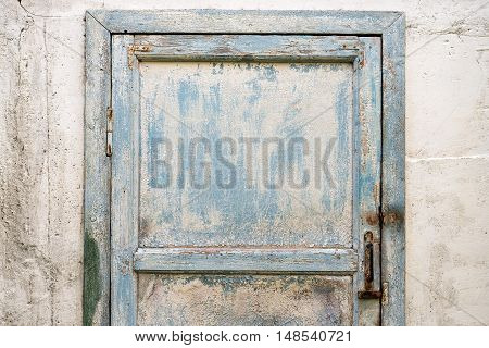 A front picture an old shabby blue door.