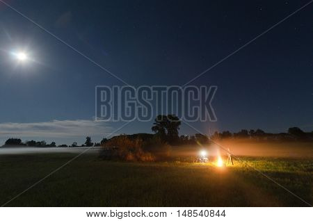 Man near fire in the moonlit night.