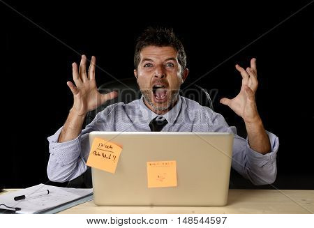 young crazy stressed businessman screaming desperate working in stress with laptop computer heavy work load isolated on office desk black background in overwork overtime concept