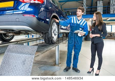 Full length of young male mechanic discussing with female customer while standing by car in garage