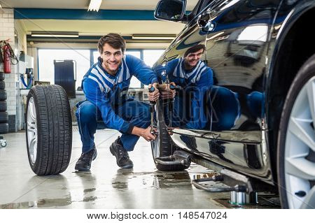 Full length of confident male mechanic crouching while changing car tire at garage