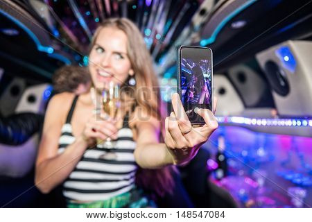 Young Woman With Champagne Flute Taking Selfie In Limo