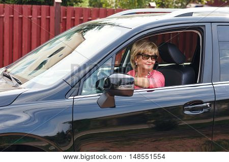 Portrait of attractive well-dressed senior woman driving a car