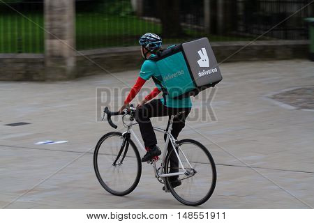 YORK, UK - SEPTEMBER 19, 2016. A cyclist from the increasingly popular take away food delivery company Deliveroo, cycling through city streets to deliver hot food to people's homes.