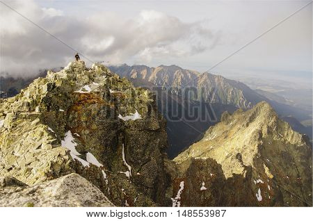 Beautiful mountain landscape. Single man stands on top of a mountain. Tatry. Rysy