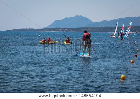 Stand Up Surfer Man Paddleboarding On Board Among Canoes And Windsurf