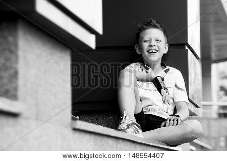 boy sitting near columns clear summer day