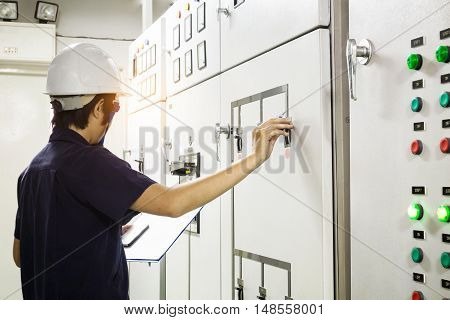 Technician is recording data Voltage or current in control panel of power plants