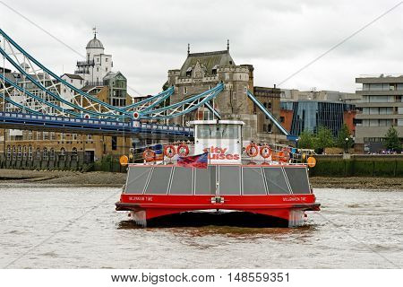 LONDON, ENGLAND - JULY 8, 2016: A City Cruises tour boat sails on the Thames River near Tower bridge. Thames is the longest river in England with 346 km (215 miles) long.