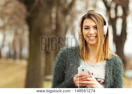 Beautiful young blonde millennial teenage girl with headphones and smart phone in park in autumn. Cool young woman listening to music outdoors in fall.