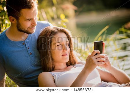 Couple dating in sunny summer nature, woman looking to mobile phone
