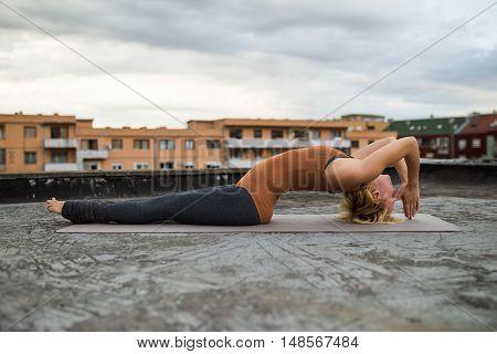 Woman practicing yoga on the roof,Fish pose/ Matsyasana