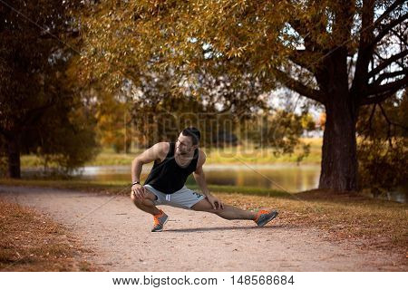 Energetic young man do exercises outdoors in park to keep their bodies in shape. Fitness concept. Body-building theme. Sport mood.