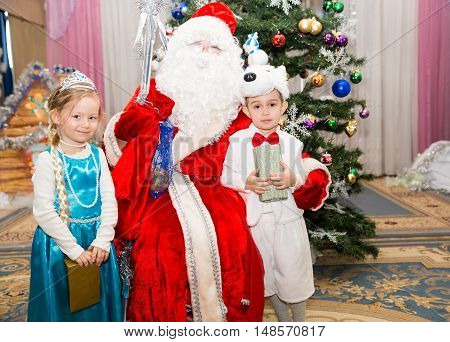 Two children dressed in carnival suits near christmas fir tree in New Year's children's holiday with gifts