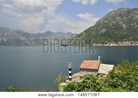 The historic Gospa od Andela Church - Our Lady of the Angels - in Kotor Bay Montenegro. The church is believed to date fom 1584 and has recently been restored. Two islands - Our Lady of the Rock and St George's Abbey - can be seen in the distance along wi