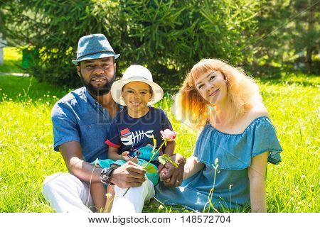 African American happy family: black father mom and baby boy on nature. Use it for a child parenting or love concept