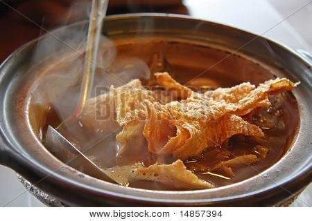 Chinese traditional herbal claypot soup hot with ladel poster